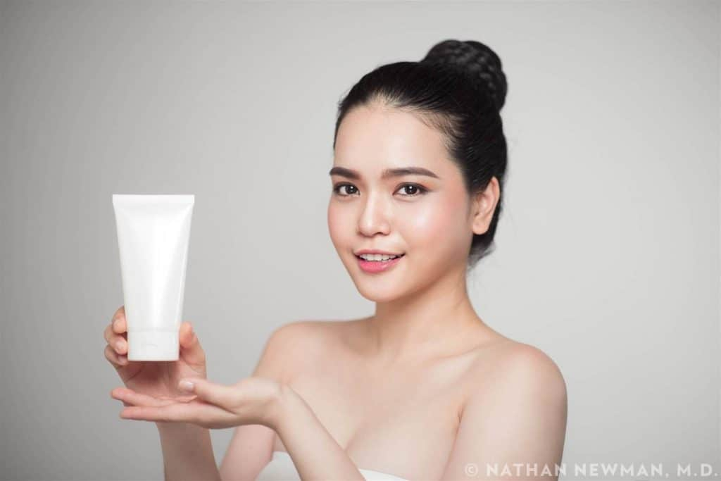 Woman with perfect skin holding cosmetic bottle