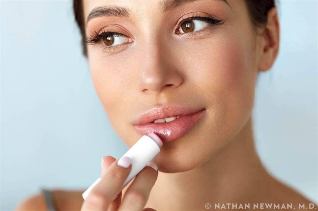 Female patient applying lip balm