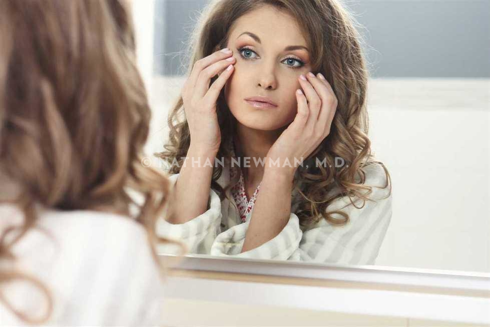 Beautiful young woman looking in the mirror and admiring her skin